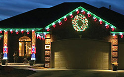 Holiday Lighting House Example from Brite Ideas with lighted toy soldiers, lighted red and green stockings and lighted wreath